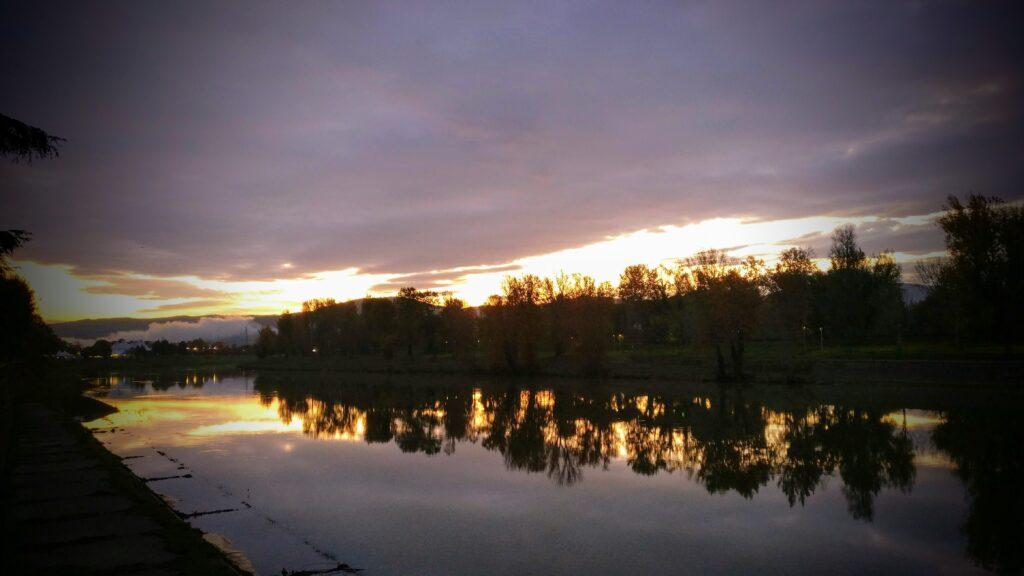 i colori dell'alba riflessi sul fiume Arno